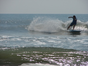 Dave throwing back a fan while surfing a waist to stomach high glassy day in South Cocoa Beach. May 14, 2011.